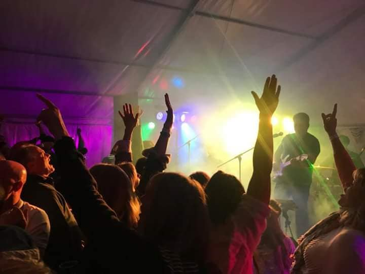 people with their hands up dancing at a party with lights and audio set up in background